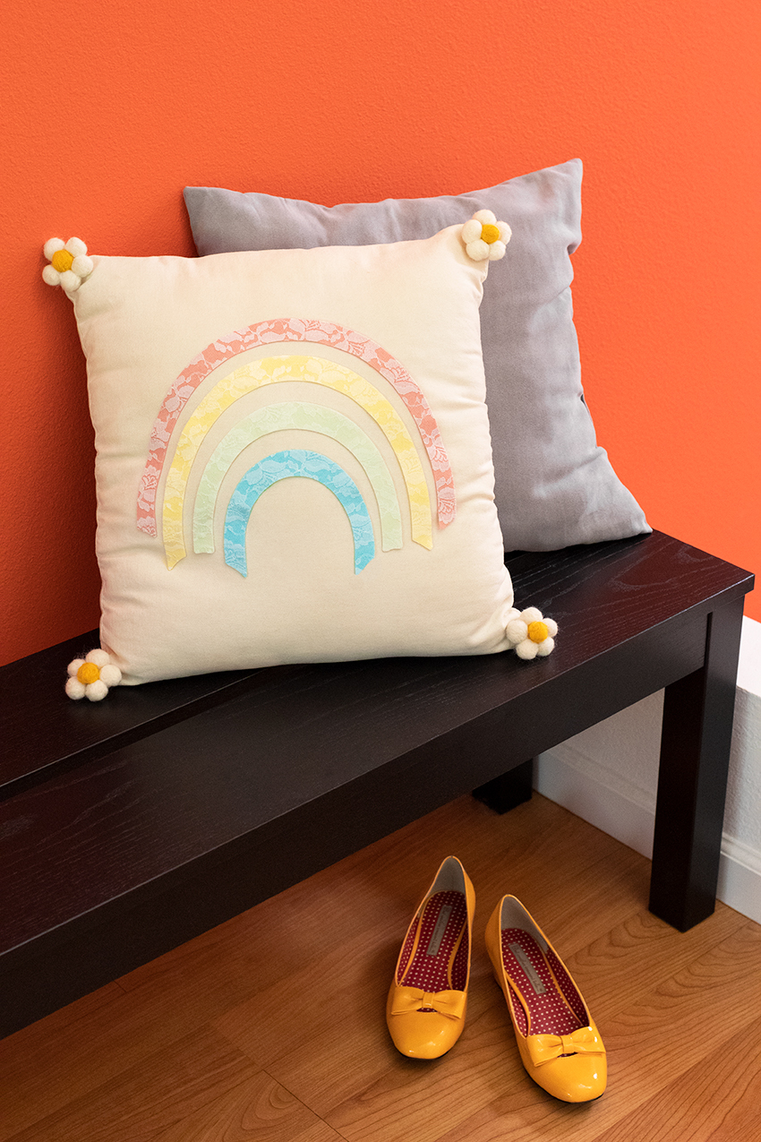 Rainbow pillow styled on a bench