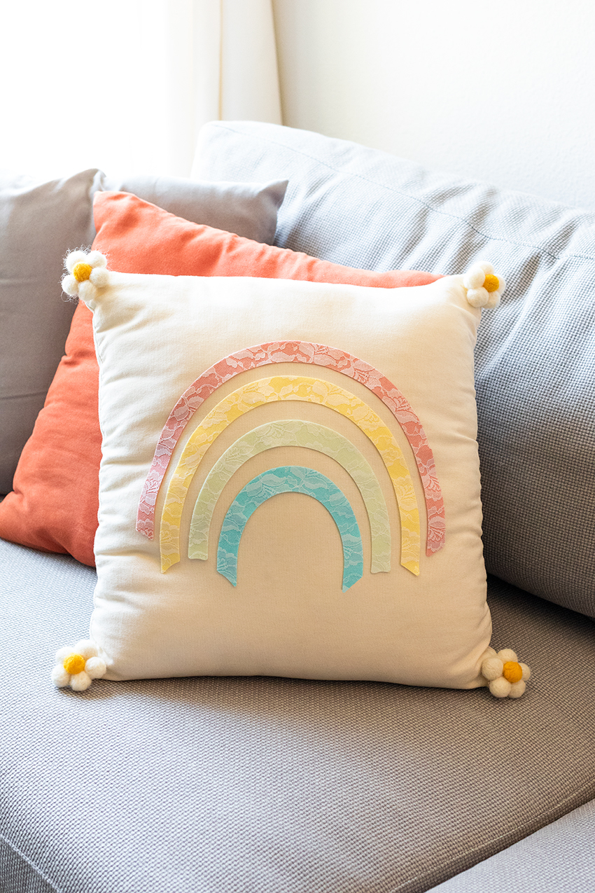 Rainbow pillow styled on a couch