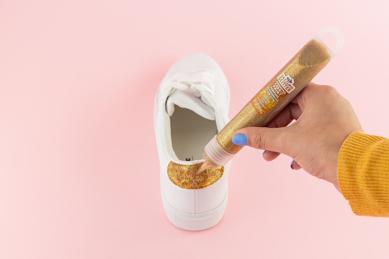 Adding gold glitter to shoes.